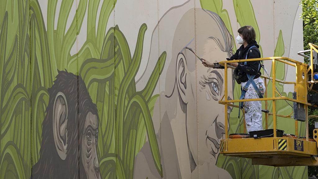 Lidia Cao ilustradora y muralista pintando el mural de Jane Goodall en BIOPARC